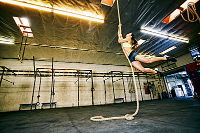 Mixed Race woman climbing rope in gymnasium - p555m1304131 by Peathegee Inc