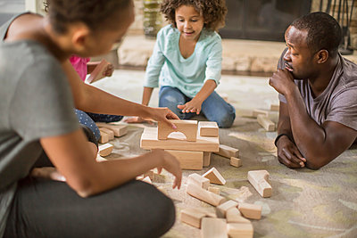 Family playing with building blocks in living room - p555m1311478 by John Fedele