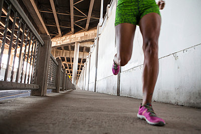 Cropped shot of young woman running on city bridge - p924m896124f by heshphoto