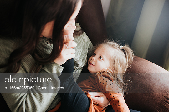 Young girl and her mother snuggle together on a chair in nursery - p1166m2255080 by Cavan Images