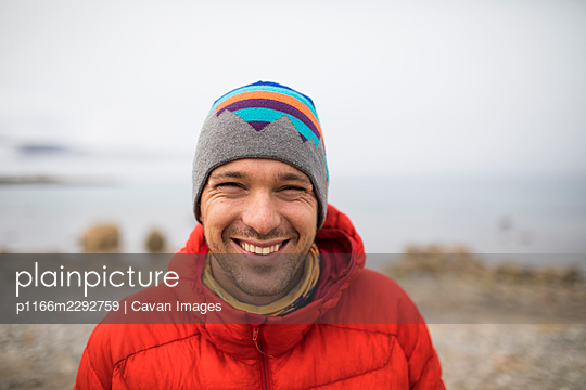 Portrait of man smiling, wearing hat and red jacket - p1166m2292759 by Cavan Images