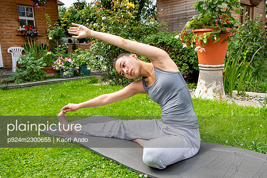 UK, London, Woman exercising on lawn in front of house - p924m2300655 by Kaori Ando