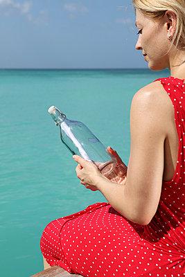 Frau hält Flaschenpost - p045m892861 von Jasmin Sander