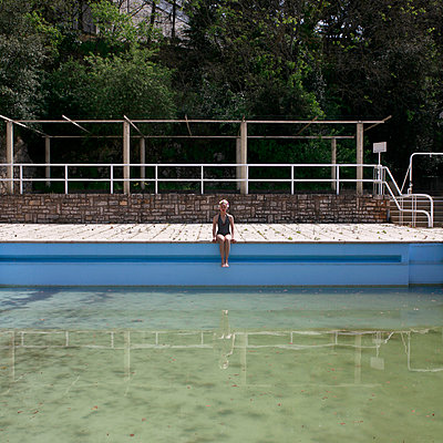 Woman sitting at the edge of outdoor pool - p1105m2082541 by Virginie Plauchut
