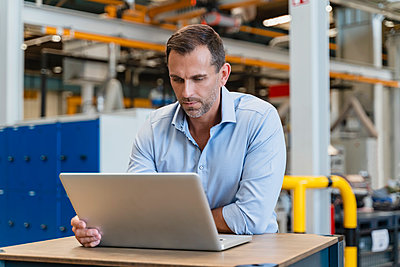 Male entrepreneur using laptop while leaning on desk in factory - p300m2240105 by Daniel Ingold