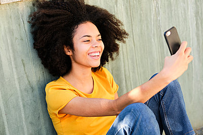 Smiling student taking selfie through mobile phone while sitting against wall - p300m2242206 by Antonio Ovejero Diaz