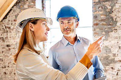 Businesswoman wearing hardhat giving instruction to building contractor while working at construction site - p300m2256457 by Peter Scholl