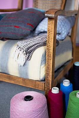 Blankets on wood framed armchair with spools of wool - p349m789750 by Brent Darby
