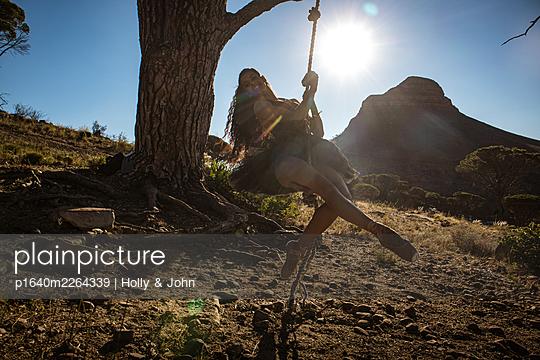 Brünette Frau schaukelt unter einem Baum - p1640m2264339 von Holly & John