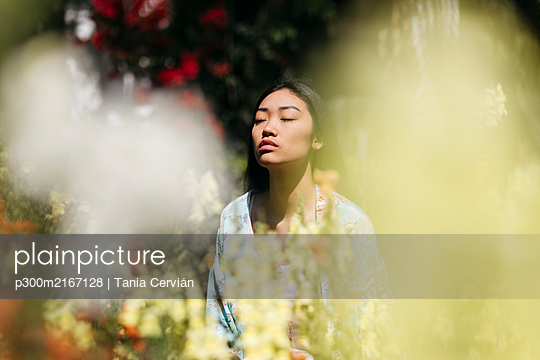 Young asian woman surrounded by flowers playing with shadows on her face - p300m2167128 von Tania Cervián