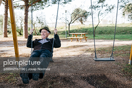 Old man swinging on playground in park - p300m2167190 by Josep Rovirosa