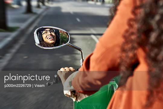 Young woman reflection on side view mirror laughing while riding motor scooter in city - p300m2226729 by Veam