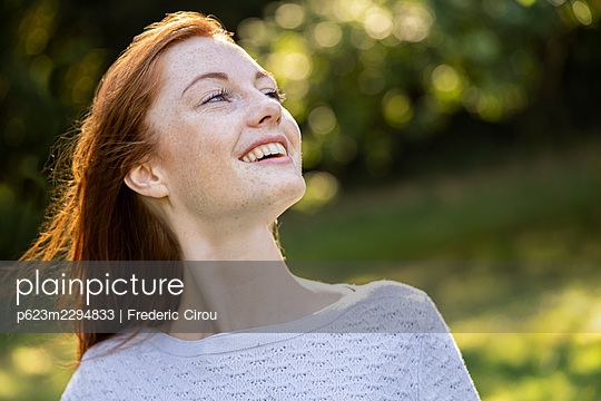 Close-up of smiling young woman in park - p623m2294833 by Frederic Cirou
