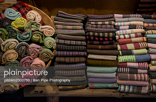 Cambodia, Siem Reap, Stacks of folded and rolled up textiles for sale - p924m2300750 by Ben Pipe Photography