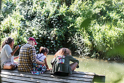 Family relaxing on dock in woods - p1023m2066677 by Sam Edwards