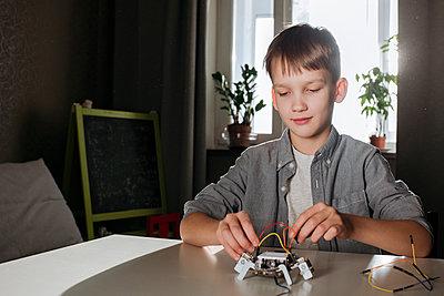 Boy assembling robot at home - p300m2170131 by Ekaterina Yakunina