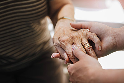 Cropped image of elderly care nurse holding hand of senior woman at nursing home - p426m2072577 by Kentaroo Tryman