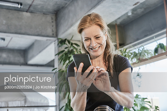 Smiling mature woman using mobile phone while sitting in loft apartment at home - p300m2265224 by Jo Kirchherr