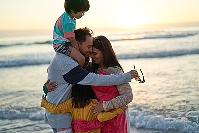 Happy affectionate family hugging on ocean beach at sunset - p1023m2200817 by Trevor Adeline