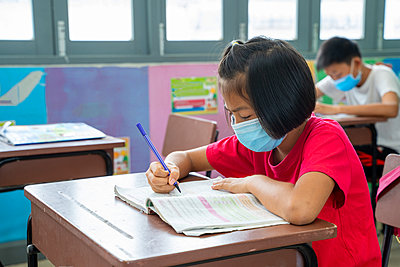 School kids wearing protective mask to Protect Against Covid-19 - p1166m2246772 by Cavan Images