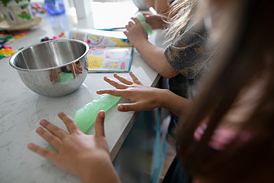 Girl friends making homemade slime in kitchen - p1192m2009456 by Hero Images