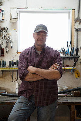 Portrait confident male farmer standing with arms crossed in workshop - p1192m2109728 by Hero Images