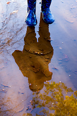 Anonymous child standing in a puddle - p1228m1511164 by Benjamin Harte