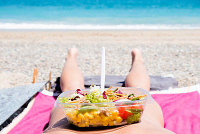 Man lying down on the beach with a salad in a plastic container in his back - p1423m2099175 by JUAN MOYANO