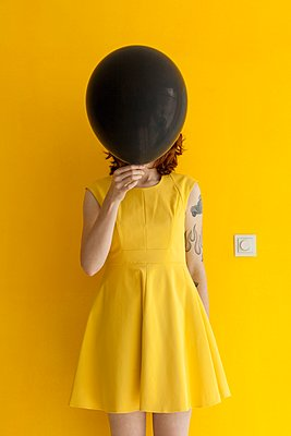 Woman in yellow dress and yellow wall with black balloon. - p896m1479519 by Rutger van der Bent