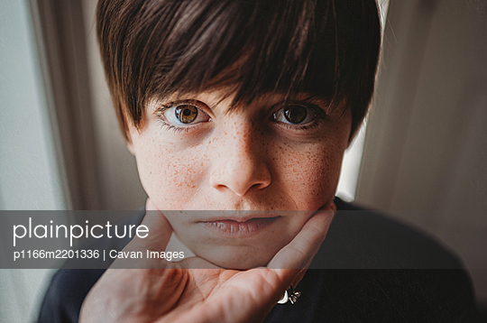 Close up of young boy's face being held under his chin by a hand. - p1166m2201336 by Cavan Images