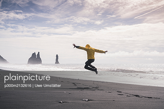 Mature man jumping for joy on a lava beach in Iceland - p300m2132616 by Uwe Umstätter