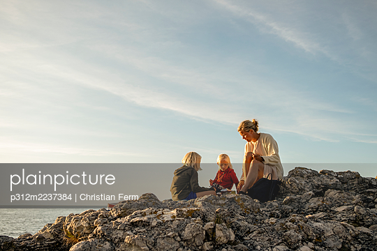 Mother with daughters sitting on rocks - p312m2237384 by Christian Ferm