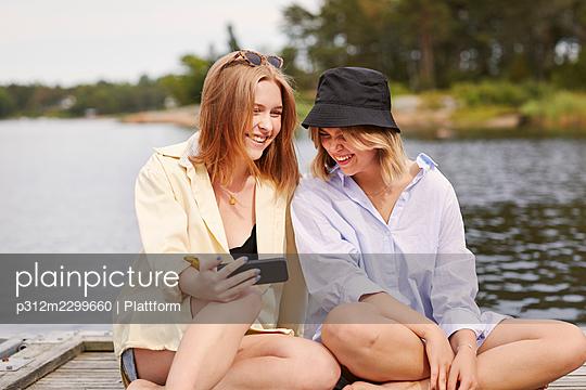 Two friends taking selfie at lakeside - p312m2299660 by Plattform