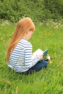 Mädchen liest Buch im Garten - p045m1031188 von Jasmin Sander