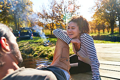 Happy young couple relaxing on sunny autumn dock - p1023m2212989 by Trevor Adeline