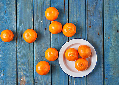Tangerines on a blue table - p1166m2095320 by Cavan Images