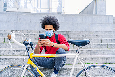 young man with afro hair sitting sending a message next to his old bicycle - p1166m2255137 by Cavan Images