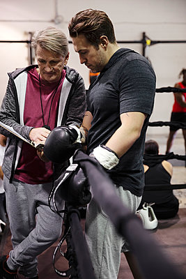 Trainer with clipboard talking to male boxer in gym - p1192m2033892 by Hero Images