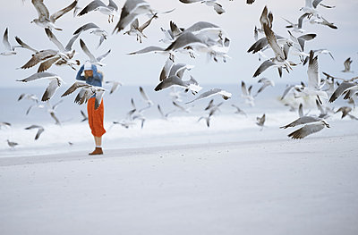 Woman next to the ocean surrounded by flying seagulls - p1577m2150325 by zhenikeyev