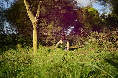 Man meditating in the grass  - p1631m2208626 by Raphaël Lorand