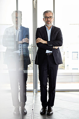 Portrait of confident businessman standing in office - p300m2012957 by Rainer Berg