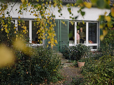 Senior couple behind windowpane of their home looking out - p300m2154975 by Gustafsson