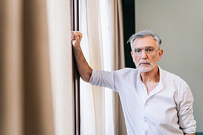 Mature man standing by window in hotel room - p300m2250496 by Daniel González