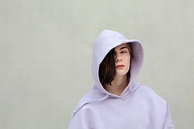 Beautiful teenage girl in hooded shirt by wall - p300m2277428 by Petra Stockhausen