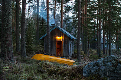 Finland, Pirkanmaa, Ruovesi, Yellow rowboat in front of wooden cottage in forest - p352m1100964f by Sami Vaskivuo