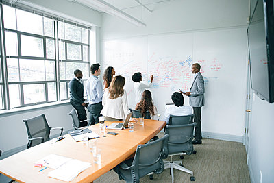 Businesswoman writing on whiteboard in meeting - p555m1504093 by John Fedele