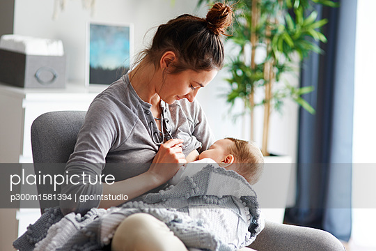 Mother breastfeeding her baby at home - p300m1581394 von gpointstudio