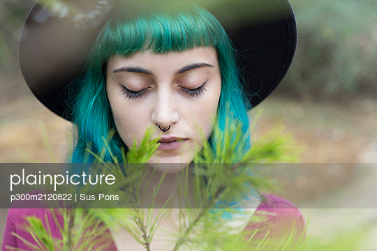 Portrait of young woman with dyed blue and green hair and nose piercing in nature - p300m2120822 by Sus Pons