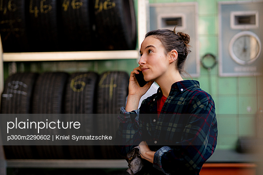 Female mechanic looking away while talking on mobile phone by tire's rack at workshop - p300m2290602 by Kniel Synnatzschke