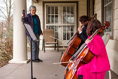 An elderly woman records two children giving cello concert on porch - p1166m2250669 by Cavan Images